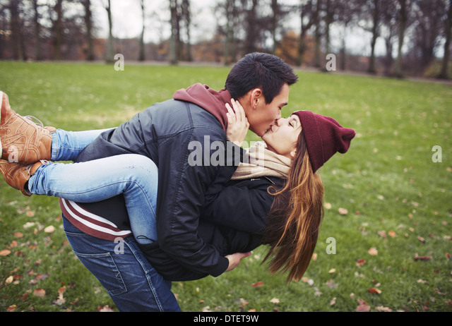 Attractive young man carrying his pretty girlfriend and kissing. Mixed race couple in love outdoors in park. - Stock Image