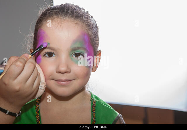 Little smiling girl making facepaint before halloween party. The make-up artist is applying some colors - Stock Image