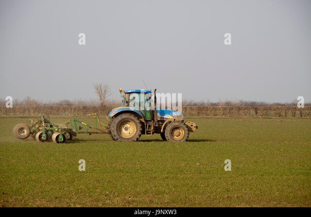 Blue tractor disc harrowing flat land - Stock Image