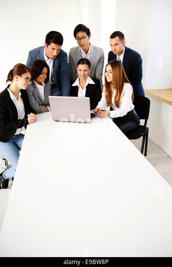 Group of a business partners using laptop together - Stock Image