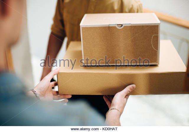 Man opening door to courier delivering parcels - Stock Image