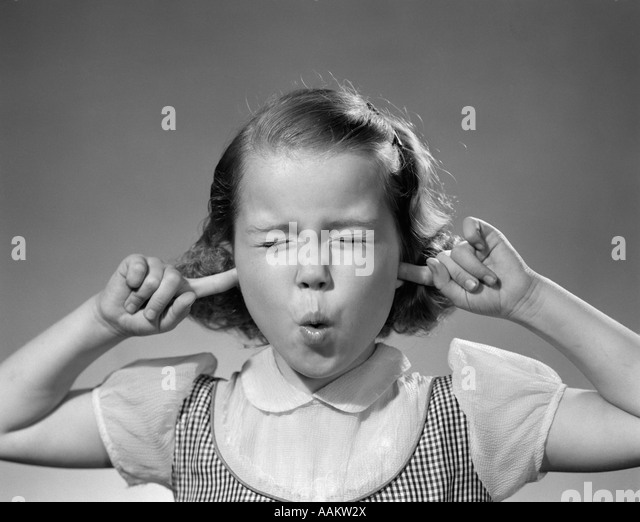 1950s GIRL WITH FINGERS IN EARS EYES CLOSED HEARING NOISE - Stock Image