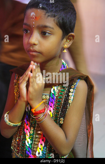 Singapore Little India Serangoon Road Sri Veeramakaliamman Temple Hindu Tamil Asian girl praying ritual - Stock Image