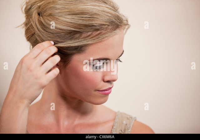 A young woman tucking her hair behind her ear - Stock Image