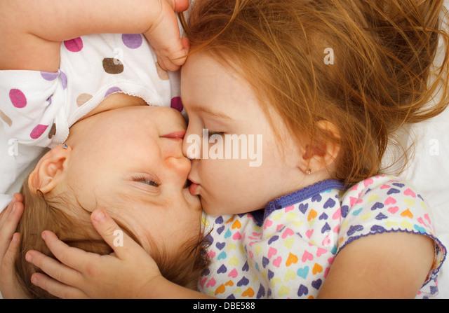Older sister kissing baby in bed - Stock-Bilder