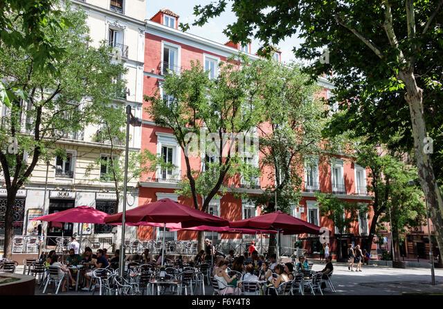 Spain Europe Spanish Hispanic Madrid Centro Chueca Calle Hortaleza restaurant alfresco dining umbrellas - Stock Image