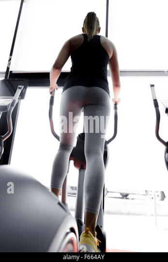 Closeup shot of legs of a female using elliptical trainer in a gym - Stock Image