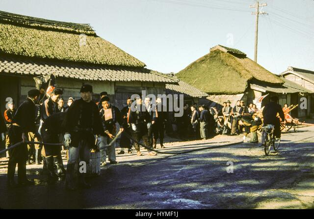 A large group of Japanese men in uniform, possible firefighters, hold a hose which extends down the street of a - Stock Image