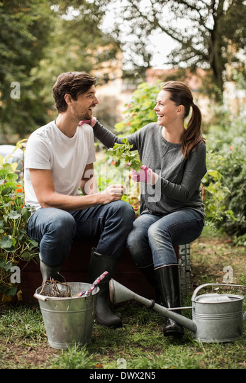 Full length of happy friends spending leisure time while gardening - Stock Image