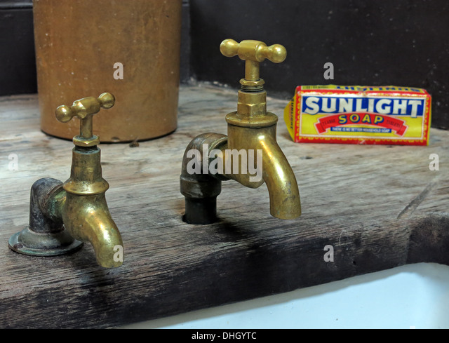 Two old historic Victorian brass taps, Lever Sunlight soap over a Belfast sink in England, UK - Stock Image