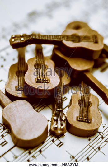 Creative musical artwork on a group of toy music instruments on melody song chart. Band of live acoustic guitars - Stock Image