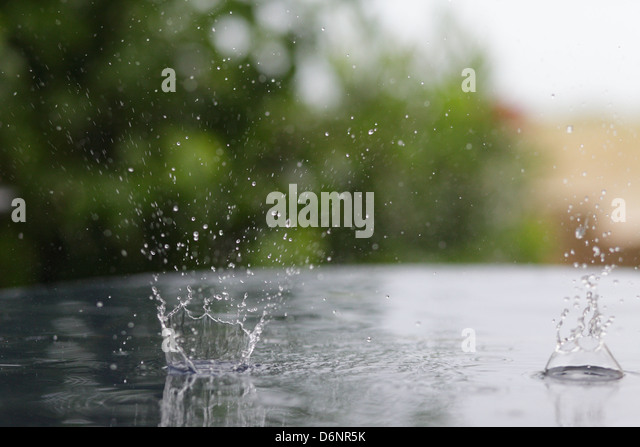 Le Barcares, France, tropical rain falling on a wet table and create impact craters - Stock Image