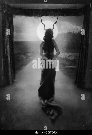 surreal picture of the back of the young standing woman with horns on her head - Stock-Bilder