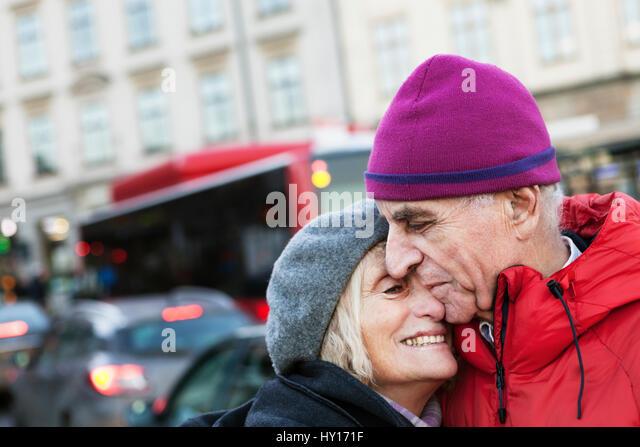 Sweden, Stockholm, Sodermalm, Senior couple hugging in street - Stock Image