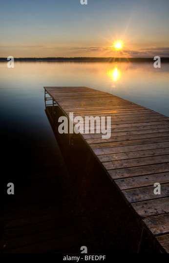 Sunset over a wooden wharf at Lake Audy, Riding Mountain National Park, Manitoba, Canada - Stock Image