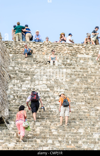Tourists climb the many steps of the Acropolis at Ek'Balam, one of the Mayan civilization ruins on Mexico's - Stock Image