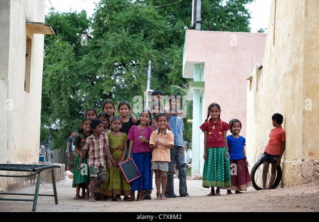 Happy young rural Indian village children smiling in the street - Stock Image