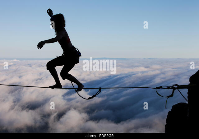 Silhouette of professional highliner Hayley Ashburn standing up on a highline above the clouds atop Mount Tamalpais - Stock Image