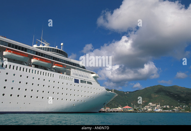 Tortola British Virgin Islands Road Town cruise ship  size comparison huge large ship dwarfs small cruise port town - Stock Image