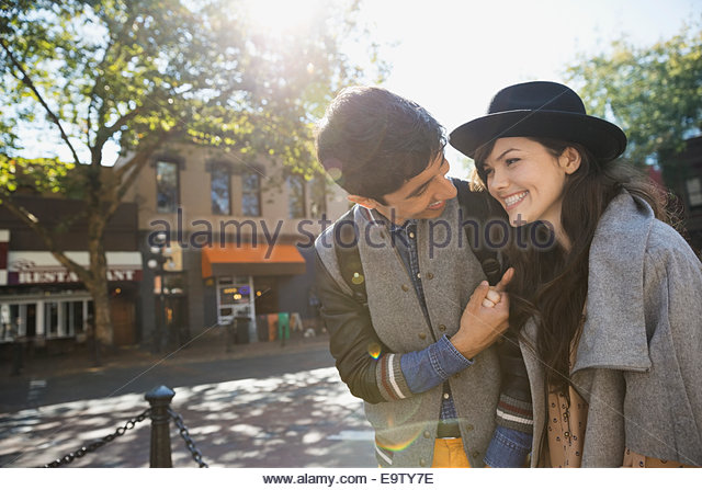 Couple laughing on sunny urban street - Stock Image