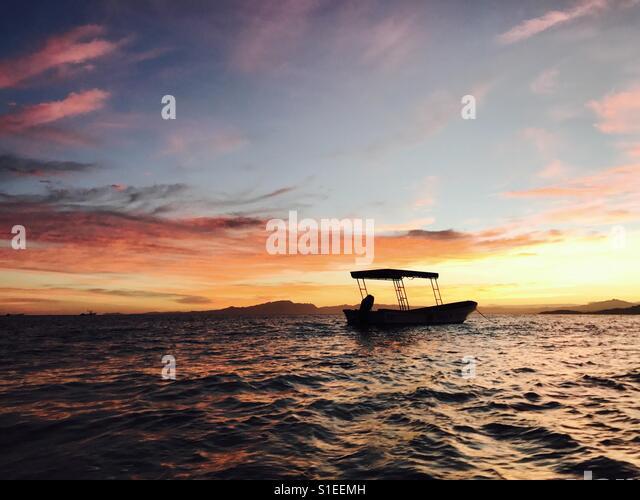 A sunset over Nadi island from Tavarua. Tavarua Island, Fiji. - Stock Image