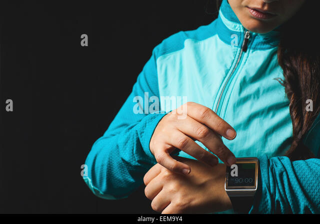 Woman wearing smart watch device on black background - Stock Image