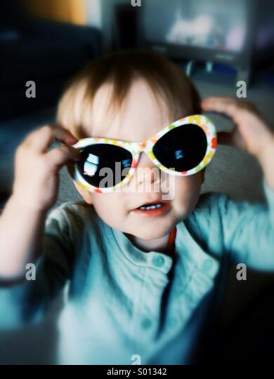 Toddler with sunglasses. - Stock Image