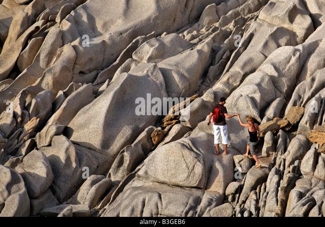 Italy Sardinia Capo Testa bizarre rock landscape couple climbing - Stock Image