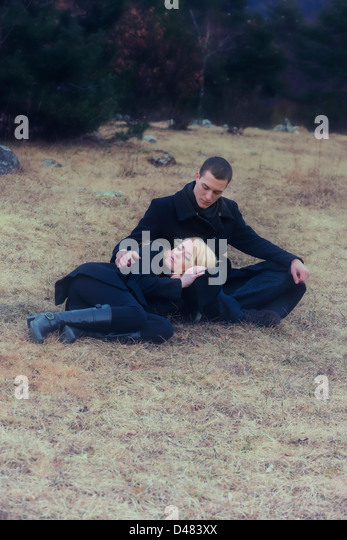 a couple in black clothes is lying on a meadow in winter - Stock-Bilder