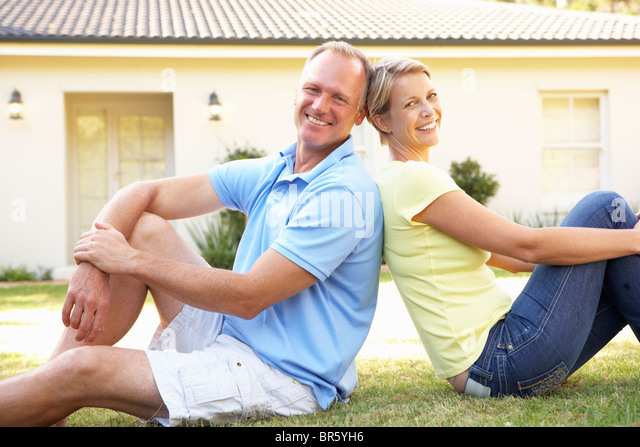 Couple Sitting Outside Dream Home - Stock Image