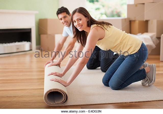 Couple unrolling carpet in new house - Stock-Bilder