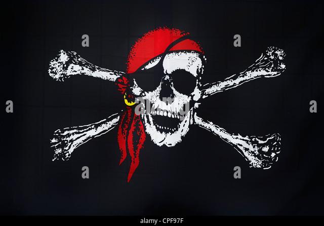 Jolly Roger pirate flag in bar window, Brixham, Devon, England - Stock Image
