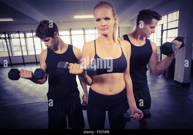 Fit people do some weightlifting together - Stock Image