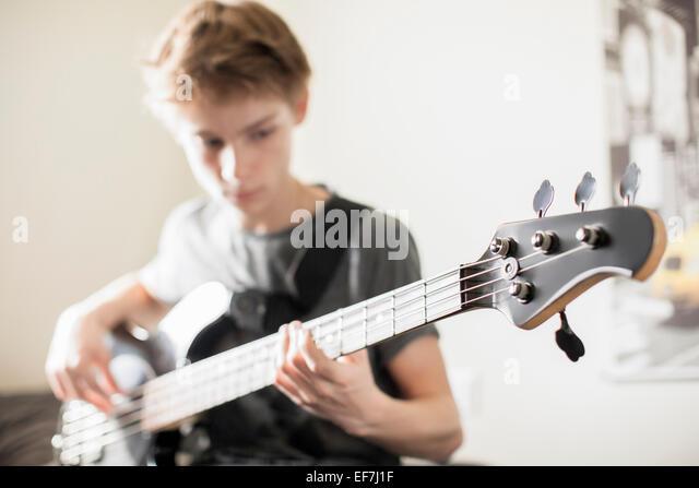 Teenage boy playing a guitar - Stock Image