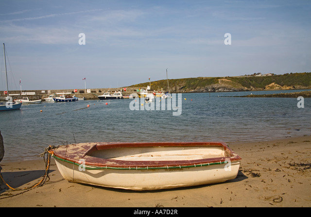 CEMAES ISLE OF ANGLESEY NORTH WALES April Looking across a beached white rowing boat towards harbour of  lovely - Stock Image