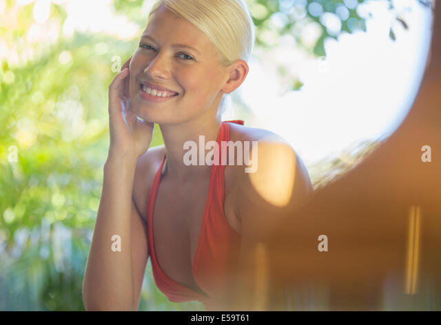 Woman resting chin in hand outdoors - Stock Image