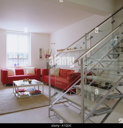 Modern living room with glass staircase and red sofas - Stock Image