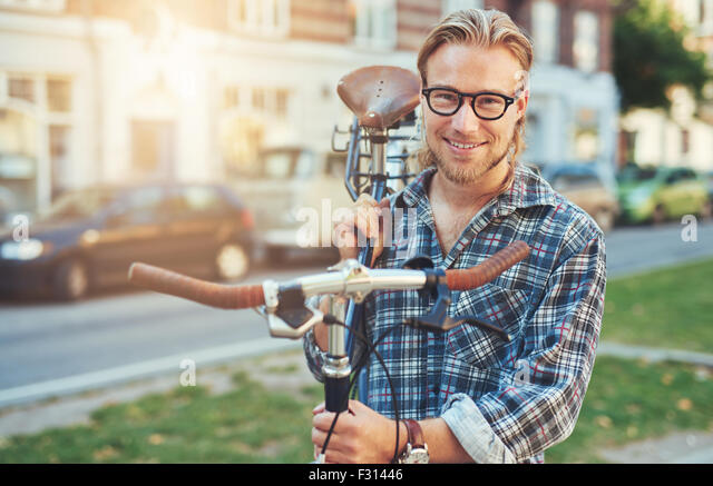 Young Man City Lifestyle. Carrying bike on his shoulder. Smiling portrait - Stock Image