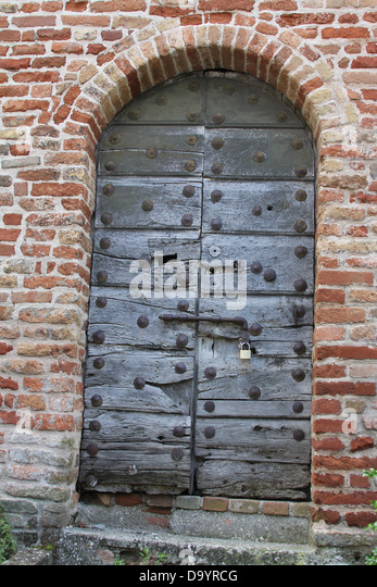 Very old iron studded  wooden door in historic wall of the old city  Amandola ,Le Marche ,Italy - Stock Image