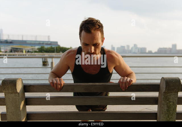 Young man doing leaning press ups on riverside park bench - Stock Image