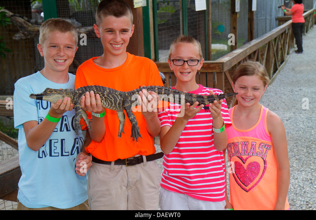 Fort Lauderdale Ft. Florida Weston Sawgrass Recreation Park Everglades baby juvenile alligator holding boy brothers - Stock Image