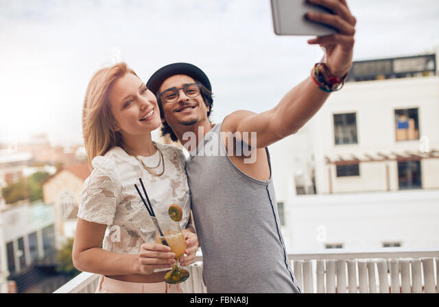 Couple of friends having a party on the rooftop taking a selfie with woman drinking cocktail. They are happy and - Stock Image
