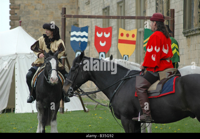 3 squires in medieval dress on horseback - Stock Image