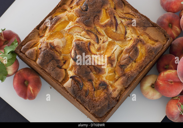A square baked peach cake on a board with fresh peaches. Fruits. Organic fresh food on a farm stand. - Stock Image