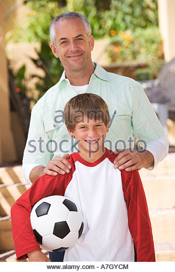 Portrait of a father with his young son, holding a football - Stock Image