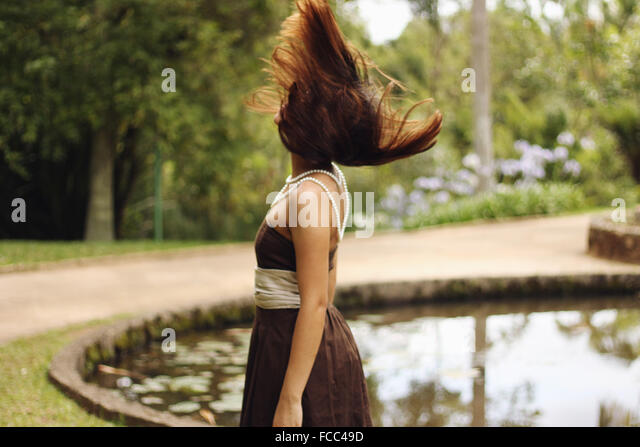 Side View Of A Woman With Blown Brown Hair By Countryside Lake - Stock Image