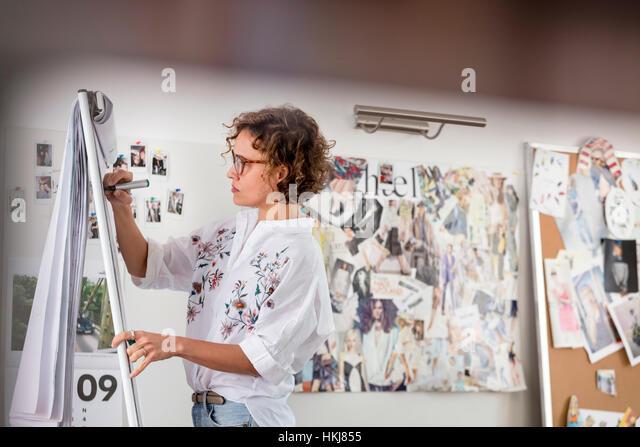 Female fashion designer brainstorming at flipchart - Stock-Bilder