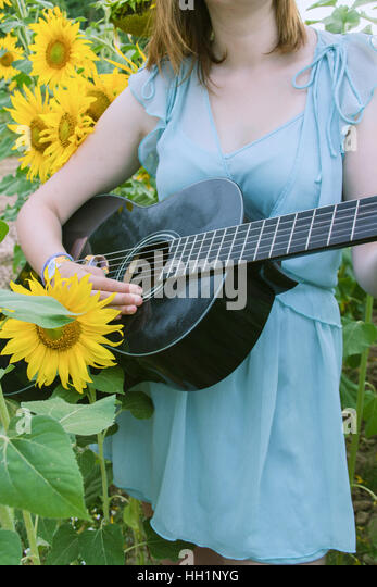 Young woman playing guitar in a field of sunflowers - Stock Image