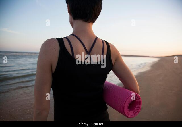 Rear view of mid adult woman preparing for yoga on beach at sunset - Stock Image