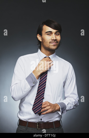 Smart young businessman adjusting his necktie looking at camera smiling. Mixed race male model getting ready for - Stock Image